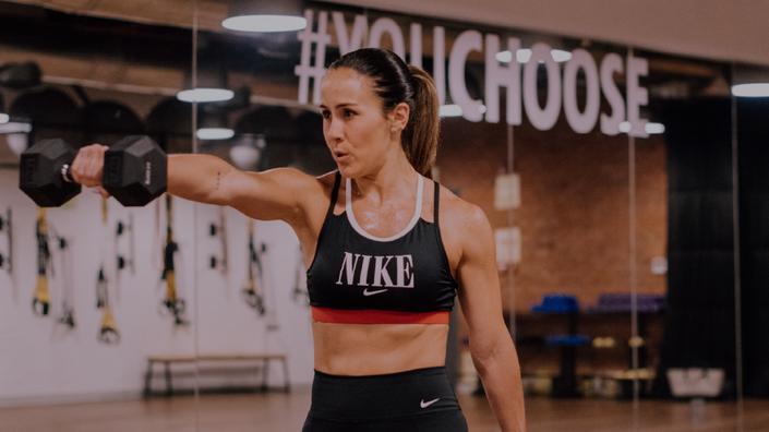 Mujer realiza entrenamiento funcional con una mancuerna en una mano y un top deportivo de Nike en una sala de entrenamiento.